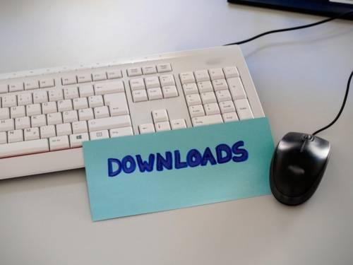 """Auf einer Tastatur liegt eine Karteikarte mit der Aufschrift """"Download"""", daneben ist ein Computermaus zu sehen."""