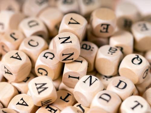 Ganz viele kleine Holzwürfel mit Buchstaben drauf, teilweise übereinander gestapelt.