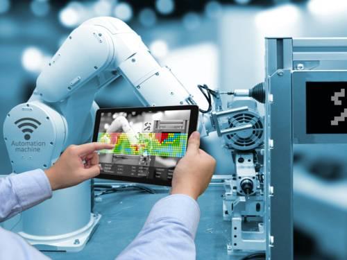 Eine Person hält einen Tablet-Computer vor einen Industrieroboter und lässt sich sich auf dem Bildschirm zusätzliche Informationen (Augmented reality) und Steuerungsmöglichkeiten einblenden.