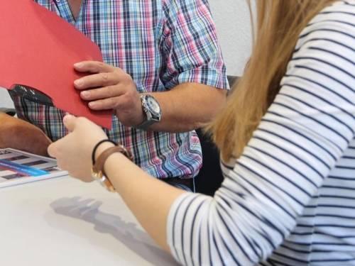 Eine Frau und ein Mann sitzen zusammen und haben eine Mappe sowie eine Broschüre bei sich.