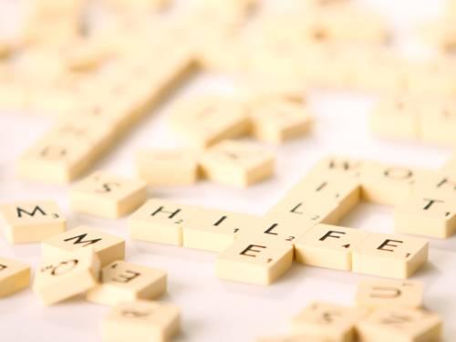 """Spielsteine tragen einzelne Buchstaben. Einige liegen durcheinander, andere bilden zum Beispiel Worte """"Hilfe"""" und """"Wille""""."""