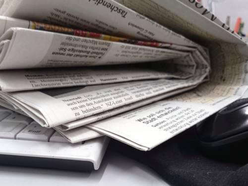 Zeitungen liegen auf einem Schreibtisch.