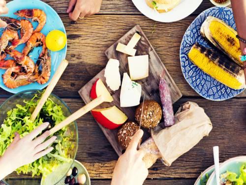 Holztisch auf dem Salat, Garnelen, Maiskolben, Wurst und Käse stehen. Hände von Personen, die sich bedienen