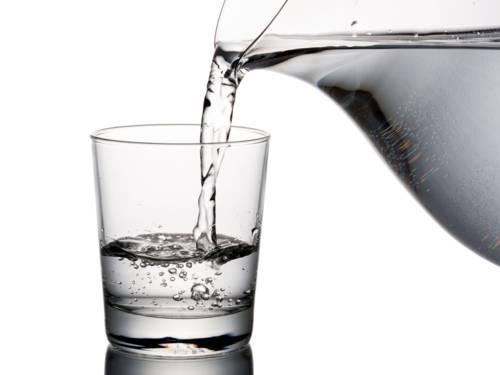 Wasser läuft aus einer Karaffe in ein Trinkglas.