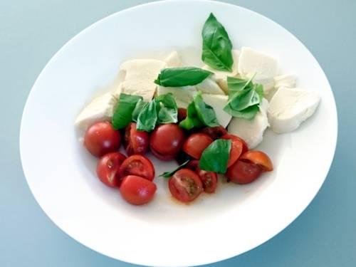Stückchen von Kirschtomaten, Mozzarella und Basilikum auf einem Teller.