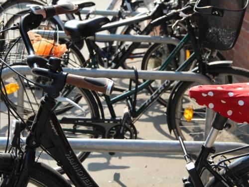 Mehrere Fahrräder, die an Fahrrädbügeln angeschlossen sind. Das Rad vorne im Bild hat einen roten Sattelüberzug mit weißen Punkten.