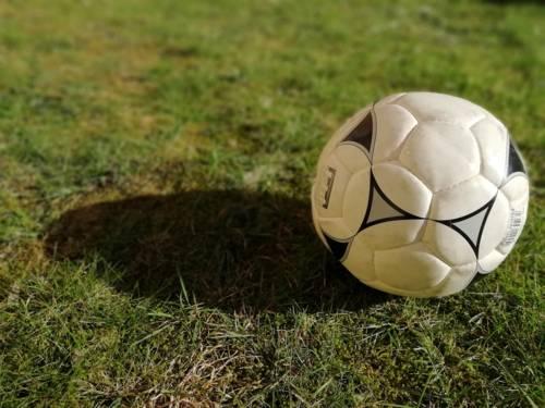 Ein Fußball, der auf einem Rasen liegt und einen Schatten wirft.