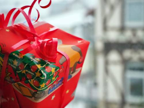 Ein Geschenk wird vor ein Fenster gehalten. Draußen sind Fachwerkhäuser und es schneit.