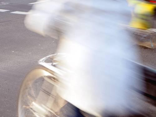 Aufnahme mit Bewegungsunschärfe und Dynamik: Der Radweg ist scharf. Die sich bewegenden Radfahrer sind bewegungsunscharf.