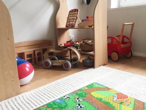 Ein Zimmer mit verschiedenen Spielsachen, unter anderem ein Laufrad, ein Puppenwagen, Wasserbälle.