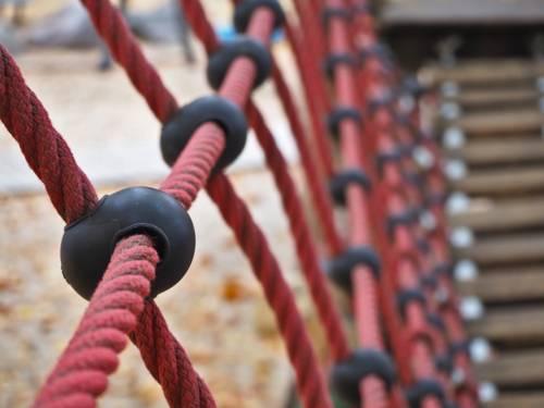 Rote Seile und Holzplanken bilden eine Hängebrücke und Geländer auf einem Spielplatz.