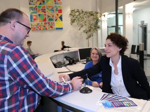 Einige Menschen an einem Tresen im Bürgerbüro der Region Hannover