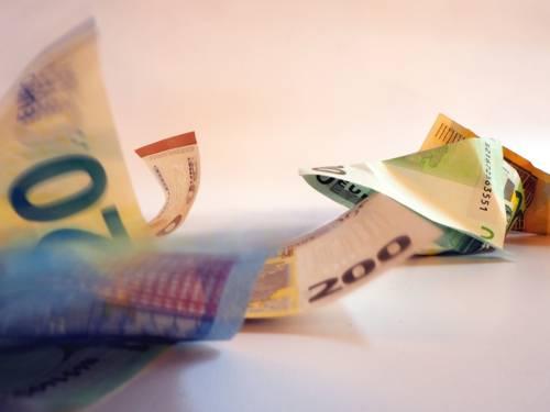 Geldscheine liegen zerknüllt vor einem weißen Hintergrund oder bewegen sich.