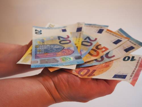 Zwei Hände tragen auf den Handflächen einen Fächer aus Geldscheinen.