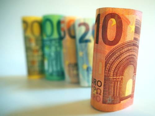 Einzelne Eurobanknoten stehen gerollt nebeneinander.