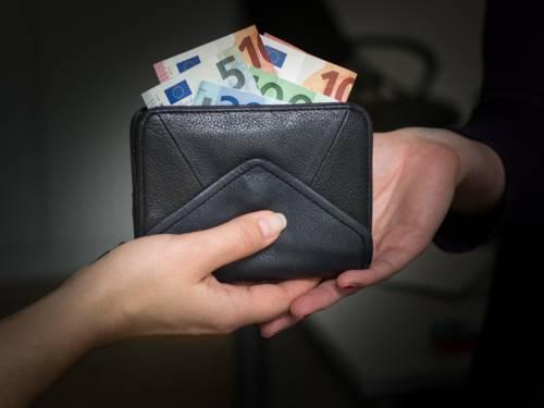 Zu sehen sind zwei Hände von zwei unterschiedlichen Personen und ein schwarzes Portemonnaie mit Eurobanknoten, das überreicht wird.