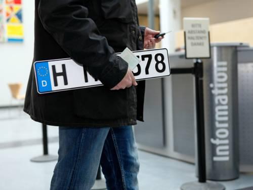 Eine Person mit einem KFZ-Kennzeichen unter dem Arm auf dem Weg zur Informationsstelle