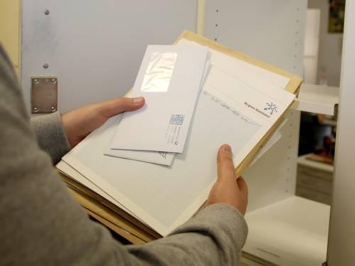 Eine Hand hält Briefumschläge verschiedener Größen.