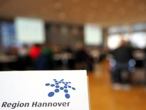 Im Vordergrund ist das Regionslogo scharf, der unscharfe Hintergrund zeigt den großen Sitzungssaal im Haus der Region Hannover, Hildesheimer Str. 18, 30169 Hannover, bei einer Veranstaltung.