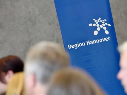 Auf einem Banner ist das Logo der Region Hannover in Weiß auf blauem Grund zu sehen. Drumherum stehen Menschen.