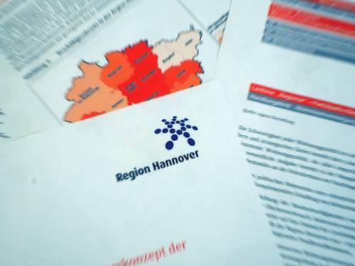 Das Logo der Region Hannover ist auf Papier gedruckt, unter der Papierseite liegen weitere Seiten mit zum Beispiel einer Karte der Region Hannover und ihrer Kommunen und Text.