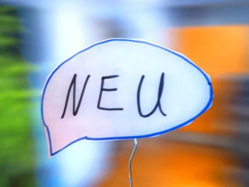"""In einer Sprechblase steht """"NEU"""", der Hintergrund ist unscharf."""