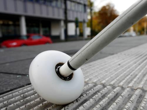 Ein weißer Langstock mit rollender Kugelspitze wird über ein Rillenplattensystem geführt.