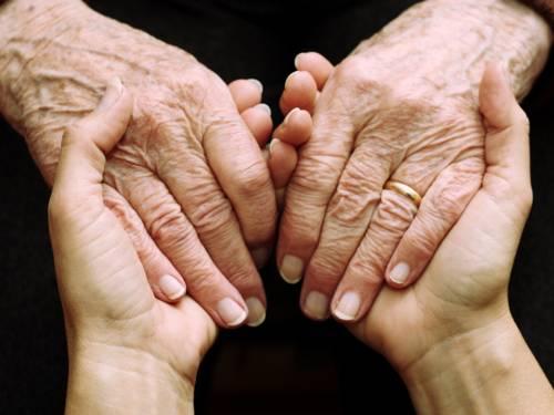 Die Hände einer jüngeren Person, die die Hände einer älteren Person halten