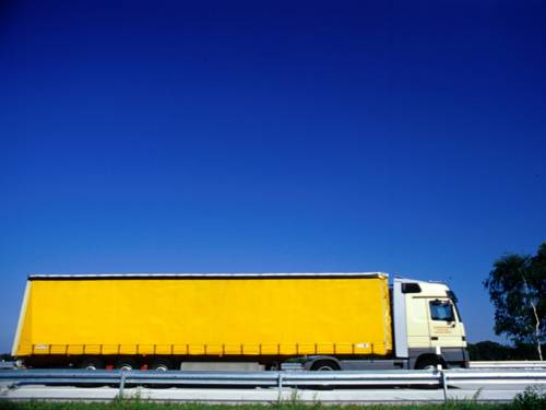 Ein gelber LKW auf einer Fahrbahn mit Leitplanken.