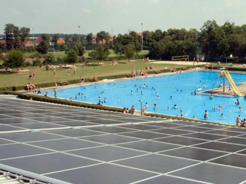 Im Vordergrund sieht der Betrachter graue Solarmodule, im Hintergrund plantschen Gäste im Außenbecken des Delfibads in Gehrden.