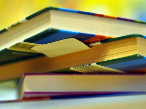 Blick von unten auf einen ungeordneten Stapel von Büchern. Sie scheinen im intensiven Gebraucht, wahrscheinlich zum Nachschlagen und Lernen. Es haftet ein Klebezettel unter einen Buch.