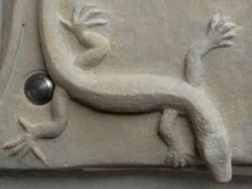 Aus Stein gearbeitete Türklingel mit einer Eidechse über dem eigentlichen Klingelknopf.
