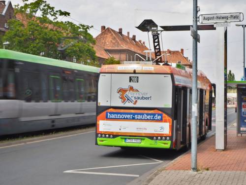 Ein Elektrobus (Rückansicht) der Linie 200 lädt an einer Ladeeinrichtung (August-Holweg-Platz)