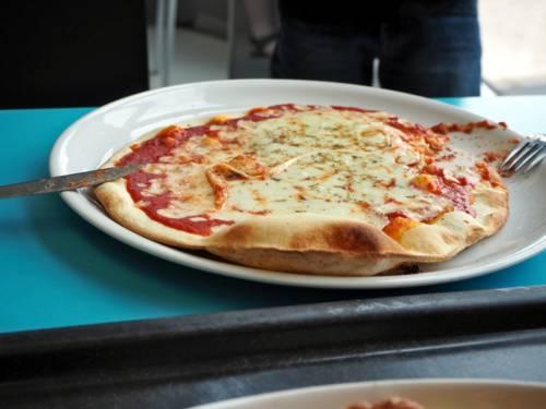 Eine verzehrbereite Pizza liegt auf einem Teller.