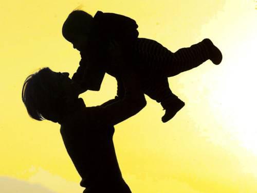Schattenumriss einer erwachsenen Person, die ein Kind in die Luft streckt.