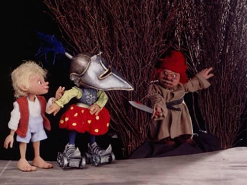 Drei Puppen auf einer Bühne.