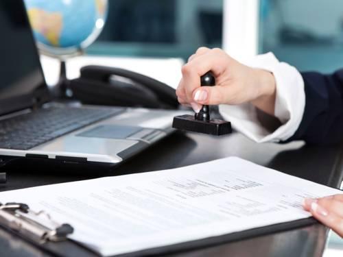 Ein Stempel wird von einer Hand über einem Antragsformular gehalten; im Hintergrund ein Laptop und eine Weltkugel.