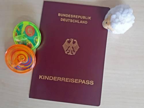Neben einem Dokument mit rotem Einband und der Aufschrift Kinderreisepass liegt Kinderspielzeug.