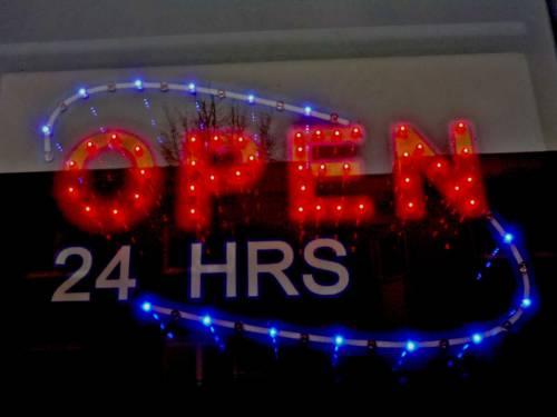 """Leuchtreklame eines Geschäftes, das mit """"open 24 hours"""" wirbt."""