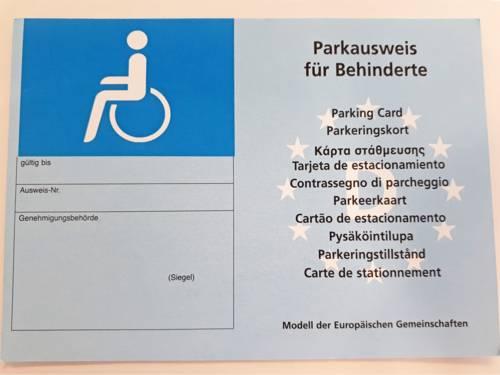 """Der Parkausweis für Behinderte zeigt links das Symbol für eine Person mit Rollstuhl, darunter die Felder """"Gültigkeit, Ausweisnummer und Genehmigungsbehörde"""". Rechts befinden sich unterhalb der Worte """"Parkausweis für Behinderte"""" Übersetzungen des Begriffs in anderen Sprachen."""