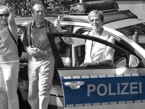 Drei Personen (zwei Frauen und ein Mann) stehen lächelnd vor einem Polizeifahrzeug. Die beiden Frauen halten den Daumen nach oben. Das Foto ist schwarz-weiß, nur die Beschriftung der Polizei ist blau eingefärbt.