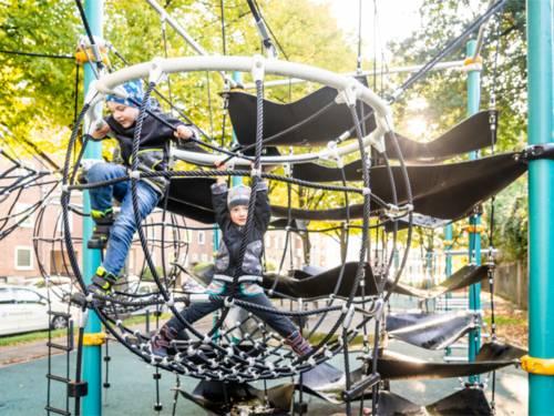Zwei spielende Kinder auf einem Klettergerüst.
