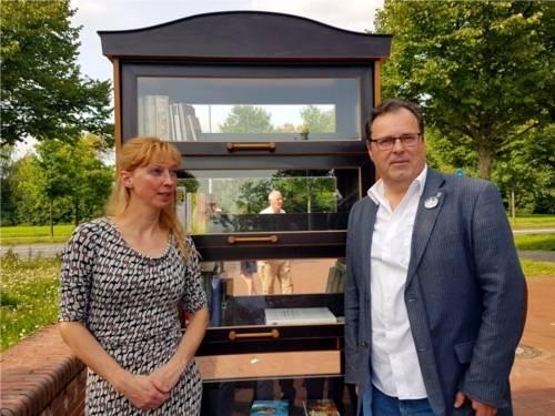 Einrichtungsleitung Die Insel, Frau Julia Heinzelmann, und Bezirksbürgermeister Rainer Göbel stehen vor dem neuen Bücherschrank.