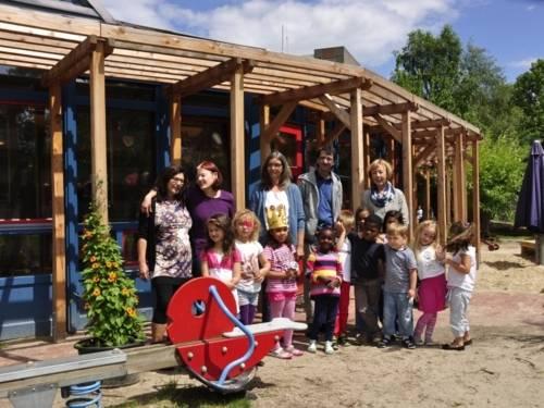 Auf dem Bild sind die Beteiligten des Beschäftigungsprojektes und die Kindergartenkinder auf dem Außengelände der Kita zu sehen. Sie stehen zusammen als Gruppe vor dem Kitagebäude (Erwachsene hinten und die Kinder stehen vor den Erwachsenen).