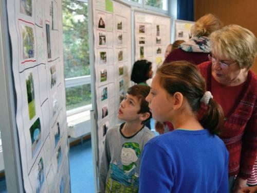 """Die Kinder der zwei Klassen der Grundschule Hägewiesen suchen gemeinsam mit ihren """"Beraterinnen"""" aus über 100 Fotos, die für sie besonderen Bilder aus. Die Bilder sind an mehreren Pinwänden befestigt."""