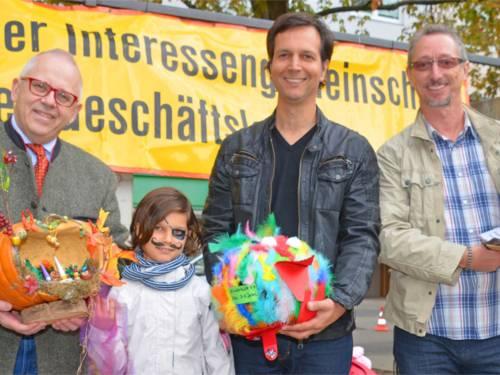 IDG Vorsitzender Michael Kellner und die Jury präsentieren die Siegerkürbisse der Kinderkiste Wichmannstraße e.V., Kinderhaus St.Petri Querstraße und die Hortgruppe der KiTa St.Bernward.