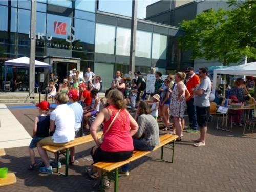 Besucherinnen und Besucher des Sommerfestes schauen sich eine Aufführung an.