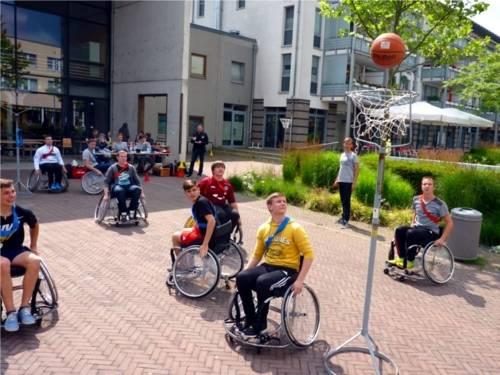 Auf dem Bild sind acht junge Rollstuhlfahrer zu sehen, die auf einem extra hergerichteten Platz mit zwei mobilen Basketballkörben Basketball spielen.