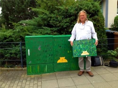 Bemalter Stromverteilerkasten mit dem Künstler Andreas Palm. In seinen Händen hält er die künstlerische Vorlage des Projektes.