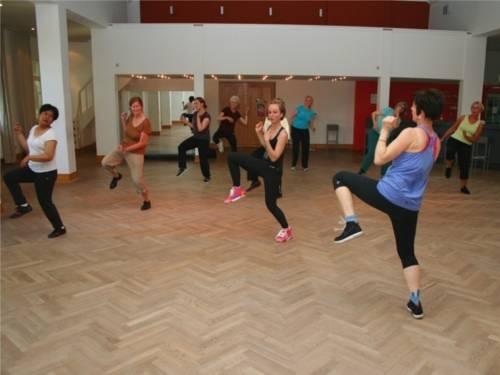Eine Tanzlehrerin tanzt vor einer Gruppe von Frauen einen Tanz vor, und die Frauen tanzen nach.